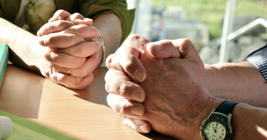 gefaltete Hände von 2 gegenüber sitzenden Personen