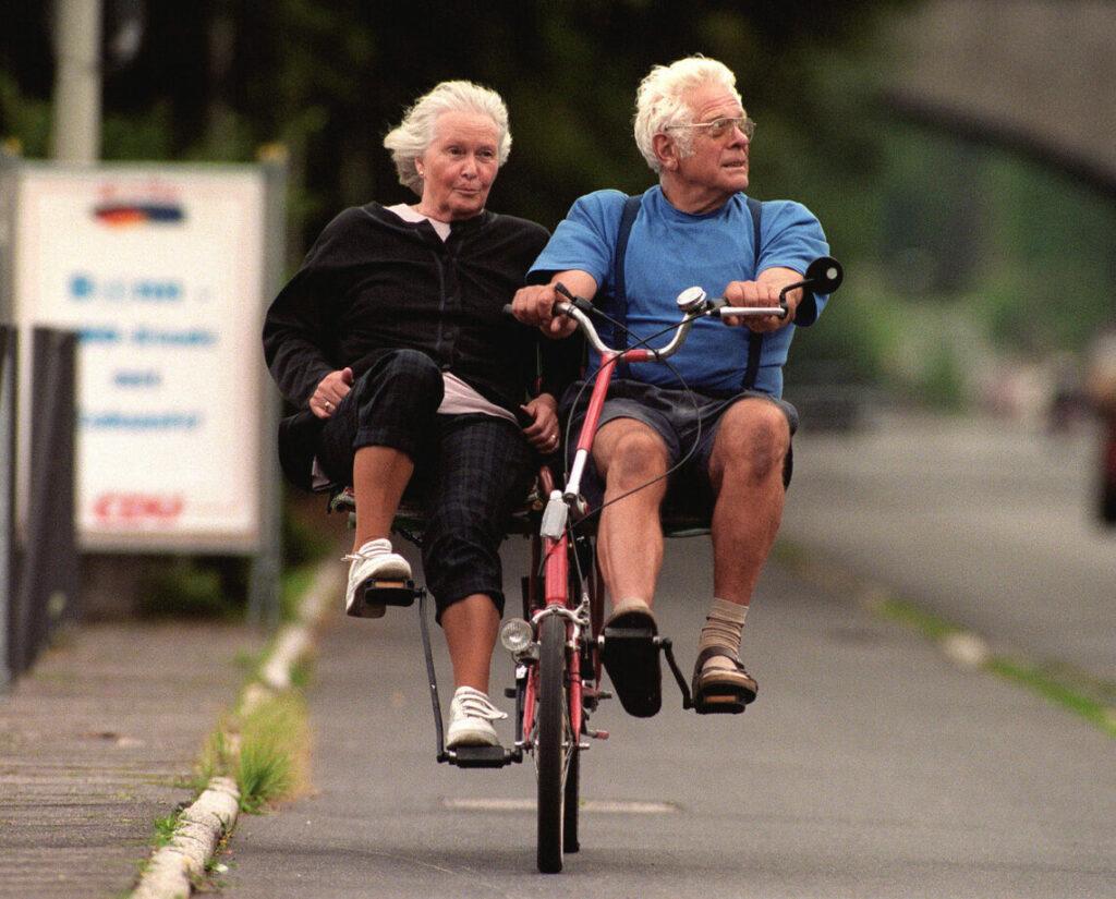 Seniorenehepaar auf einem selbstgebastelten Tandem