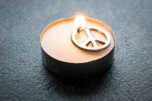 Friedenssymbol im Teelicht