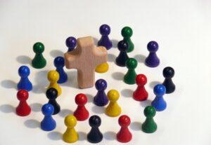 Verschiedenfarbige Spielfiguren aus Gesellschaftsspielen stehen um ein kleines Holzkreuz