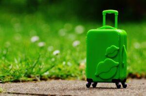 grüner Rollkoffer vor grünem Hintergrund