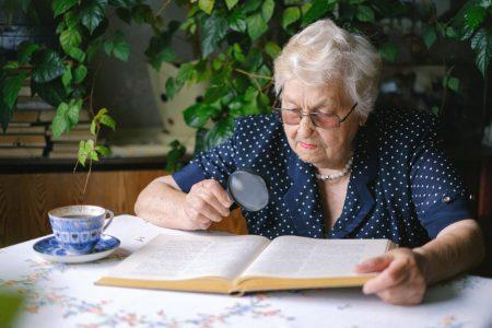 alte Frau liest mit Lupe